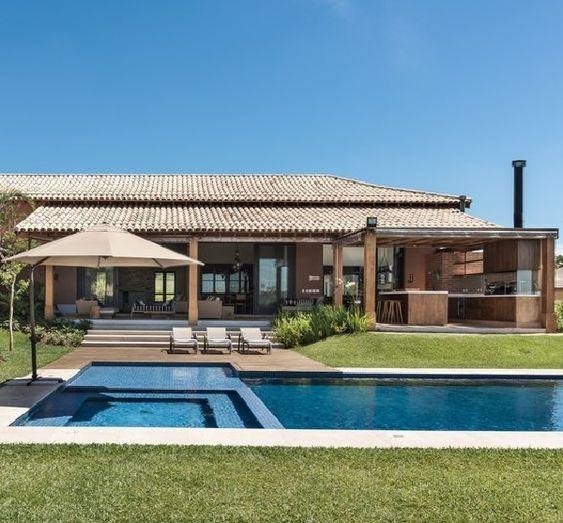Casa cinza com área de lazer e piscina.