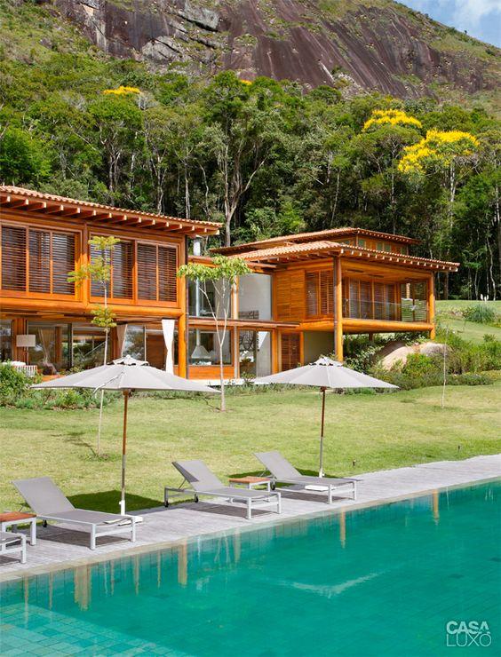Casa com estrutura de madeira em frente a área de piscina