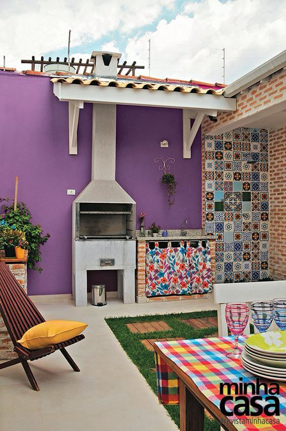 Área externa supercolorida com parede roxa e azulejo português.