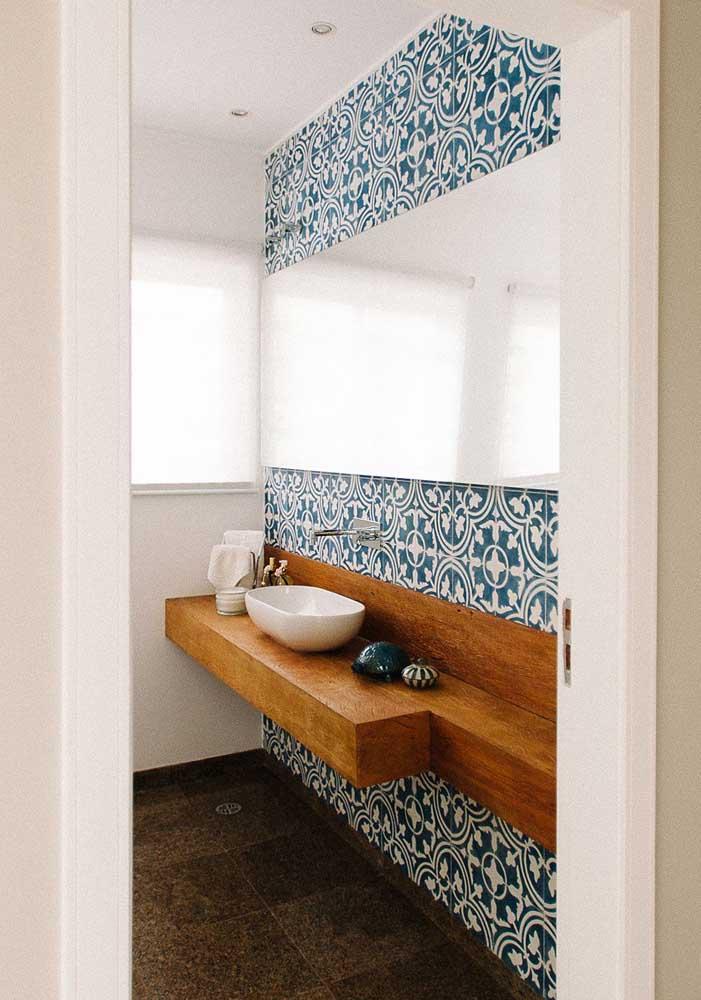 Banheiro com revestimento atemporal em azul e branco.