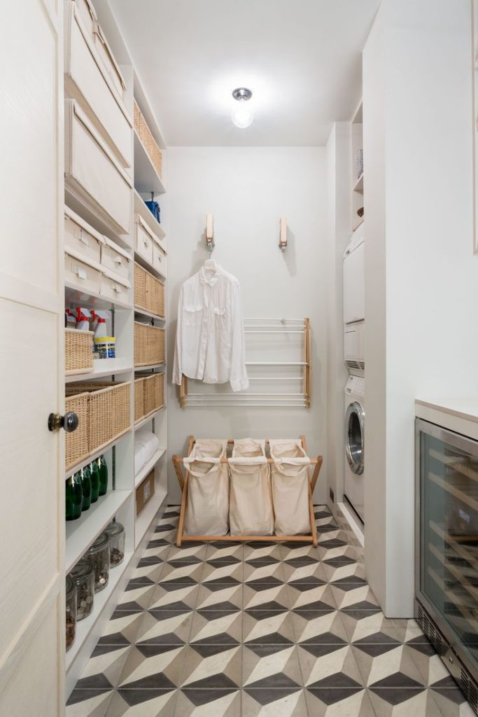 Área de serviço decorada com cestos e prateleiras.