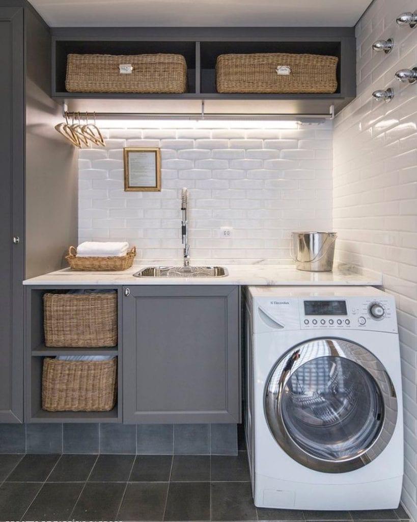 Área de serviço com armário clássico e azulejo de tijolinho branco.
