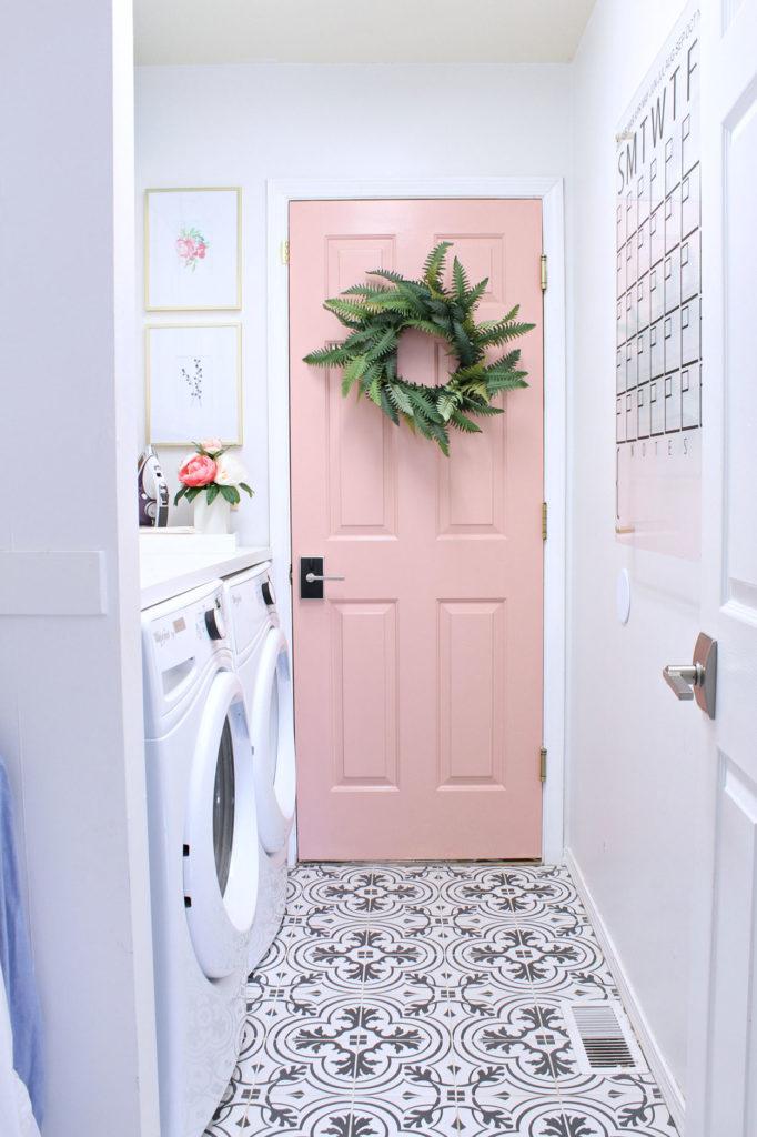 Área de serviço pequena e delicada com porta rosa e quadros decorativos.