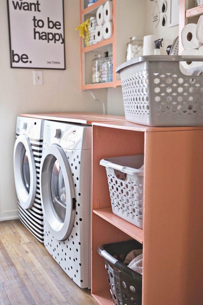 Área de serviço simples com armários coloridos e quadro decorativo.