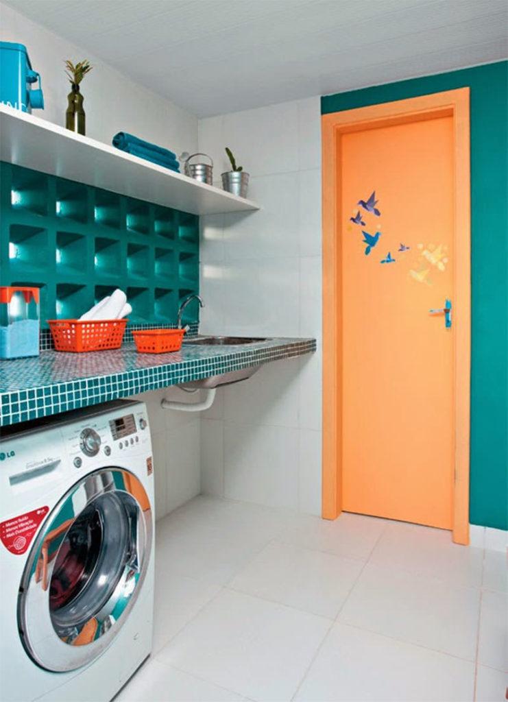 Decoração com pastilhas azuis e porta laranja.