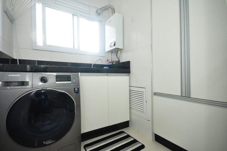 Área de serviço simples com armários brancas.