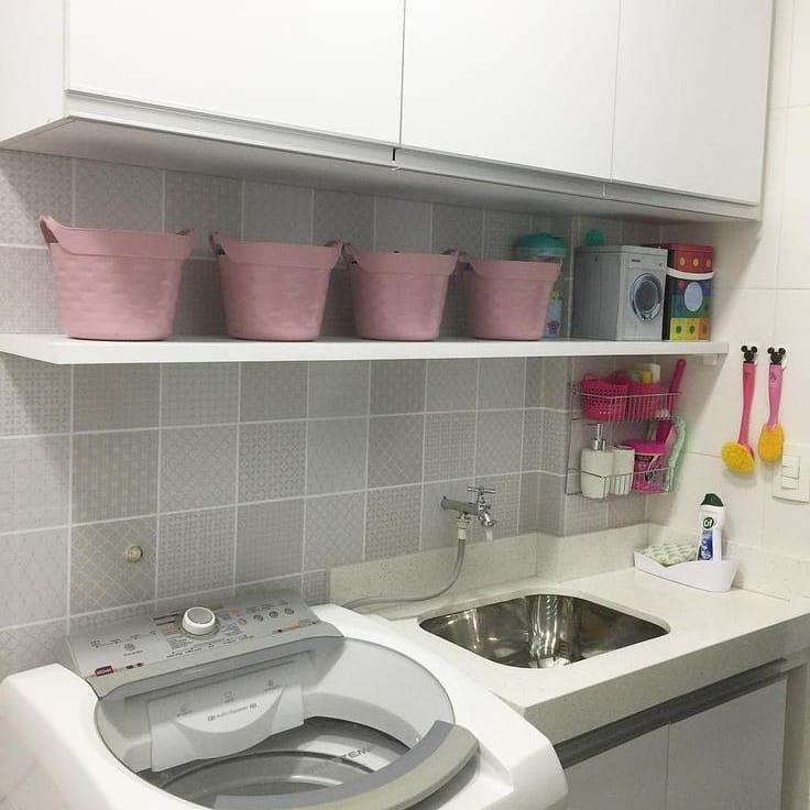 Área de serviço simples com prateleira e cestos rosas.
