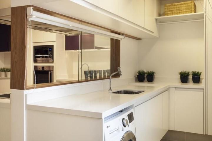 Área de serviço simples com armários brancos e bancada de silestone.