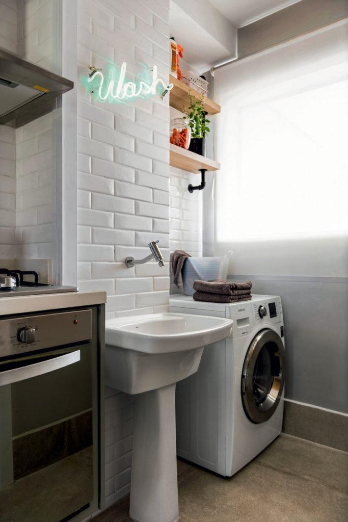 Área de serviço simples com prateleiras e azulejos de tijolinho branco.