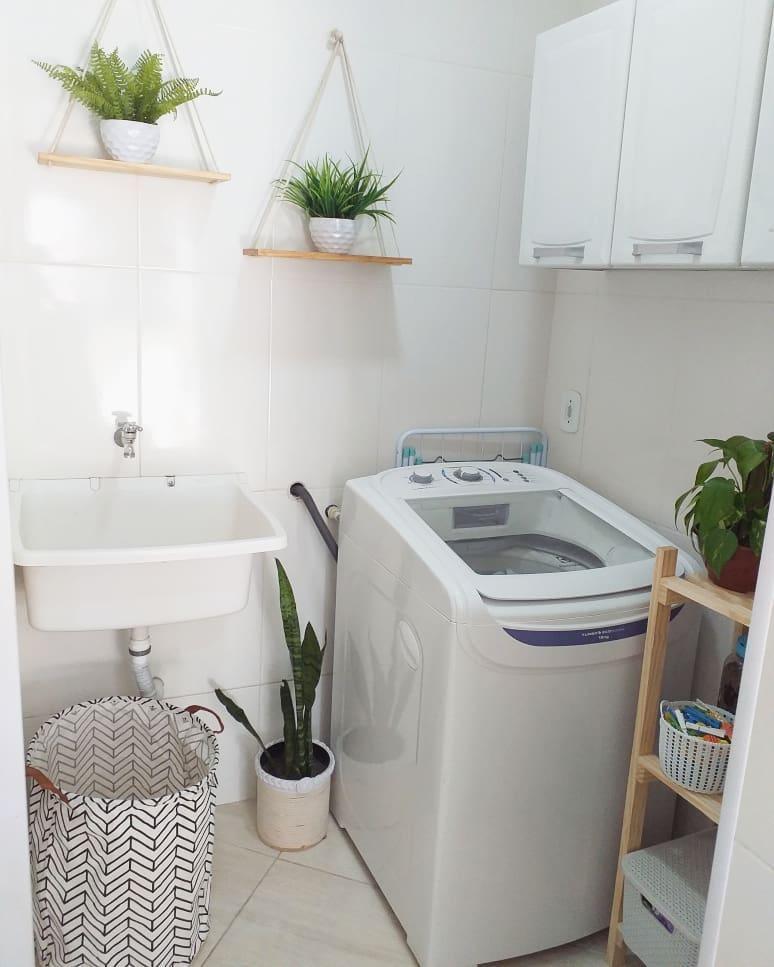 Área de serviço simples com armário branco e vasos de planta.