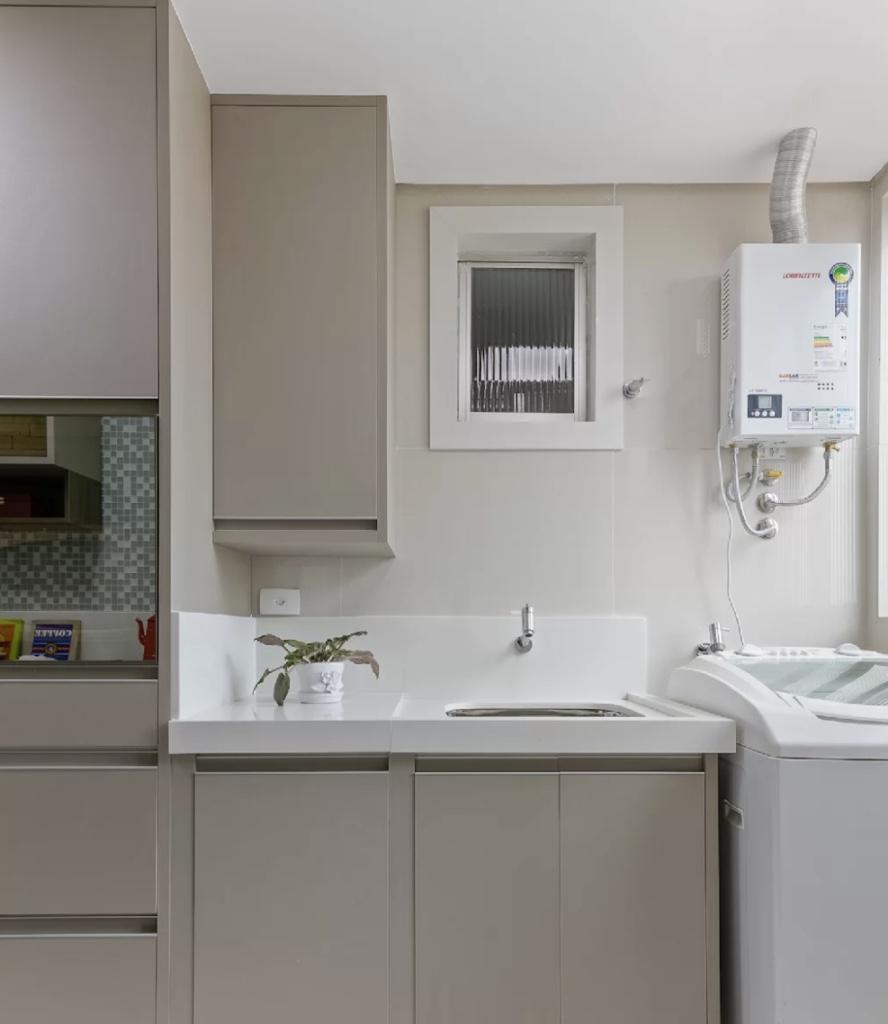 Área de serviço pequena com armários cinzas.