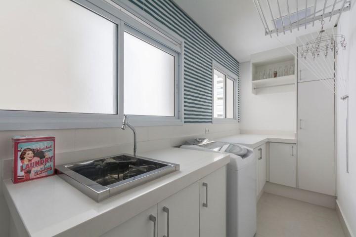 Área de serviço grande com decoração simples e branca.