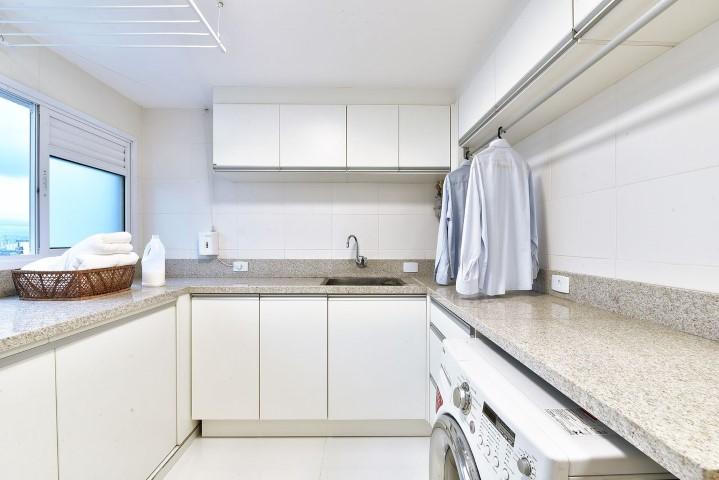 Decoração branca com armários simples e bancada de granito.