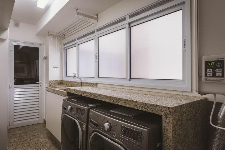 Decoração simples com bancada de granito e máquinas de lavar roupa.