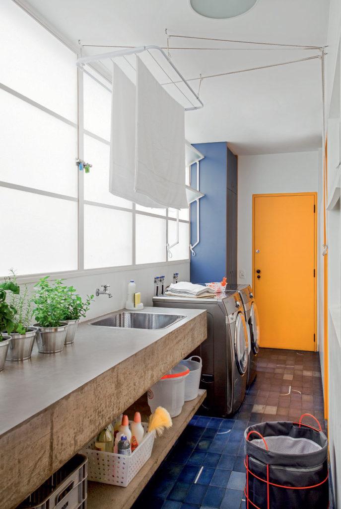 Decoração moderna com bancada de cimento e armários azuis.