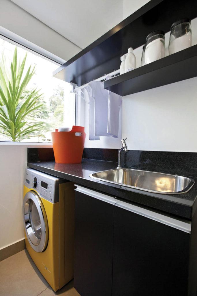 Decoração com armários pretos e máquina de lavar roupa amarela.
