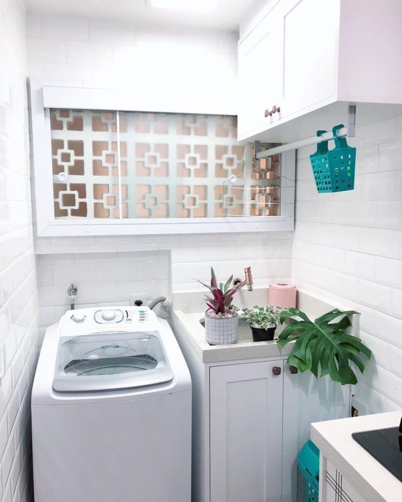 Área de serviço simples com azulejo de tijolinho branco e armário suspenso.