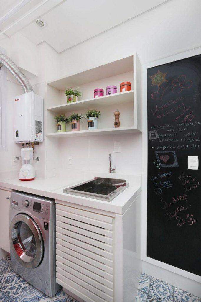 Área de serviço com armários brancos e parede com tinta de lousa.
