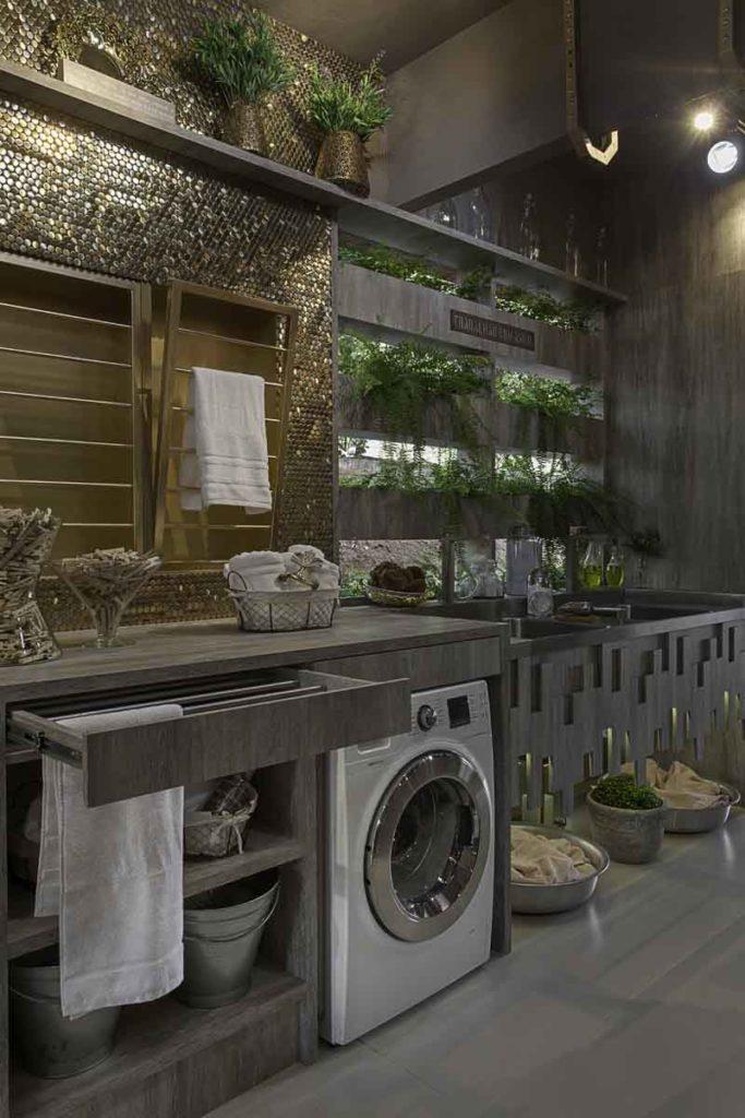 Área de serviço moderna com armários cinzas e pastillhas douradas.
