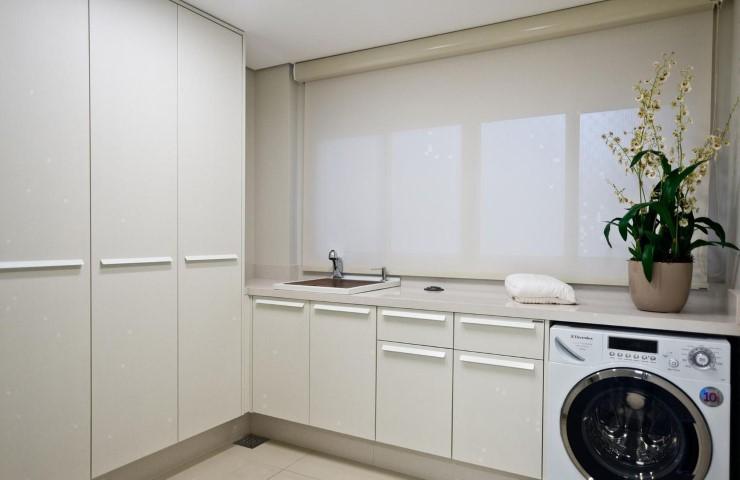 Área de serviço simples e grande com armário branco.