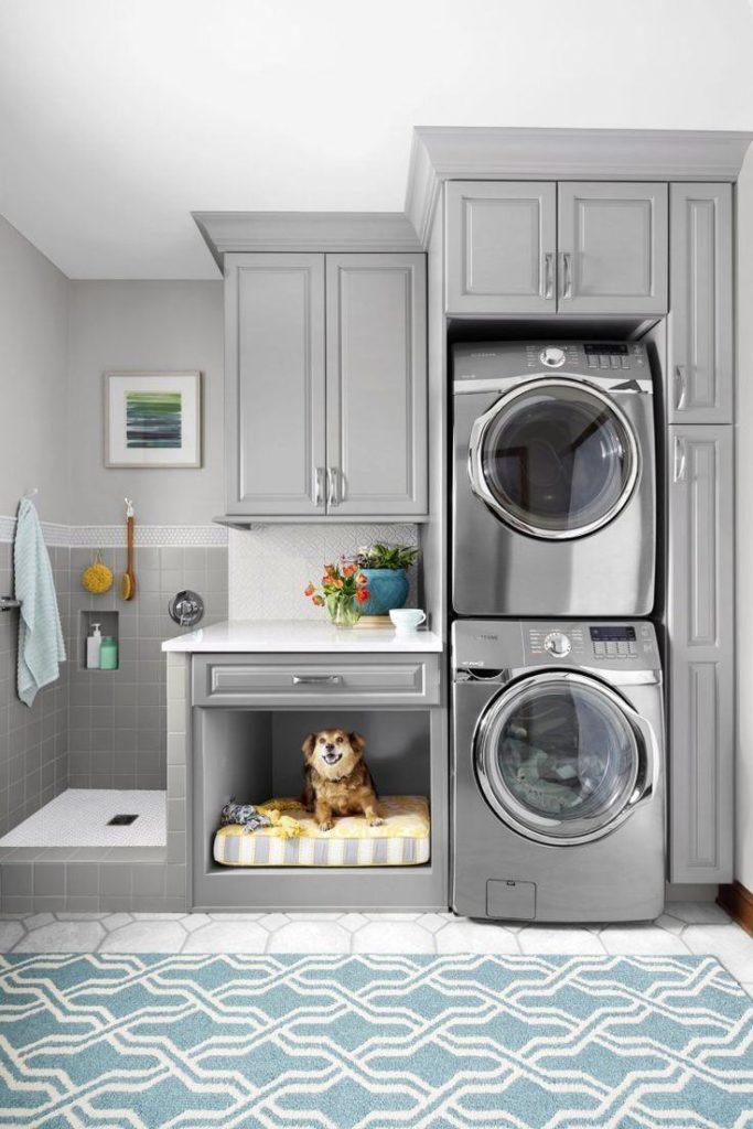 Área de serviço decorada com cama para cachorro e máquina de lavar roupa.