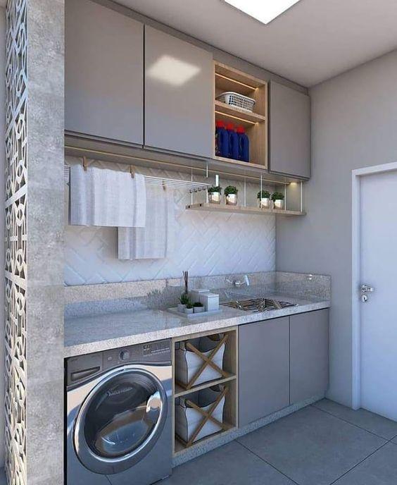 Área de serviço simples com armários cinzas e nichos de madeira.