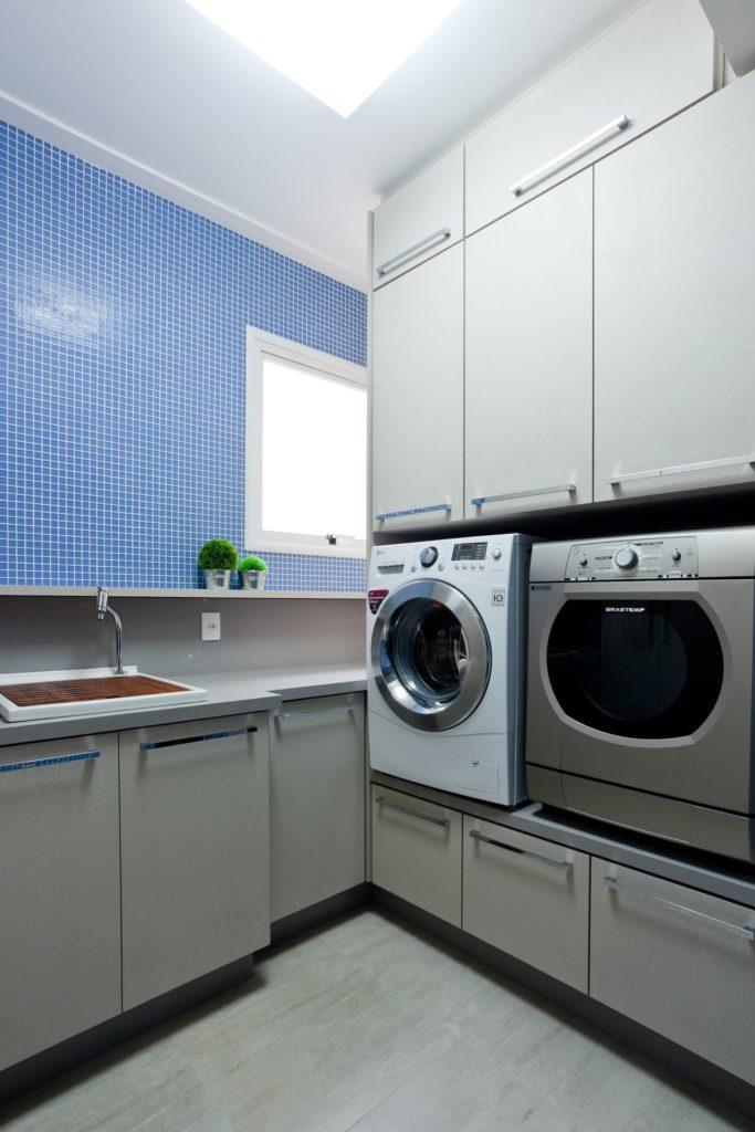 Área de serviço simples com armários cinzas e pastilhas azuis.
