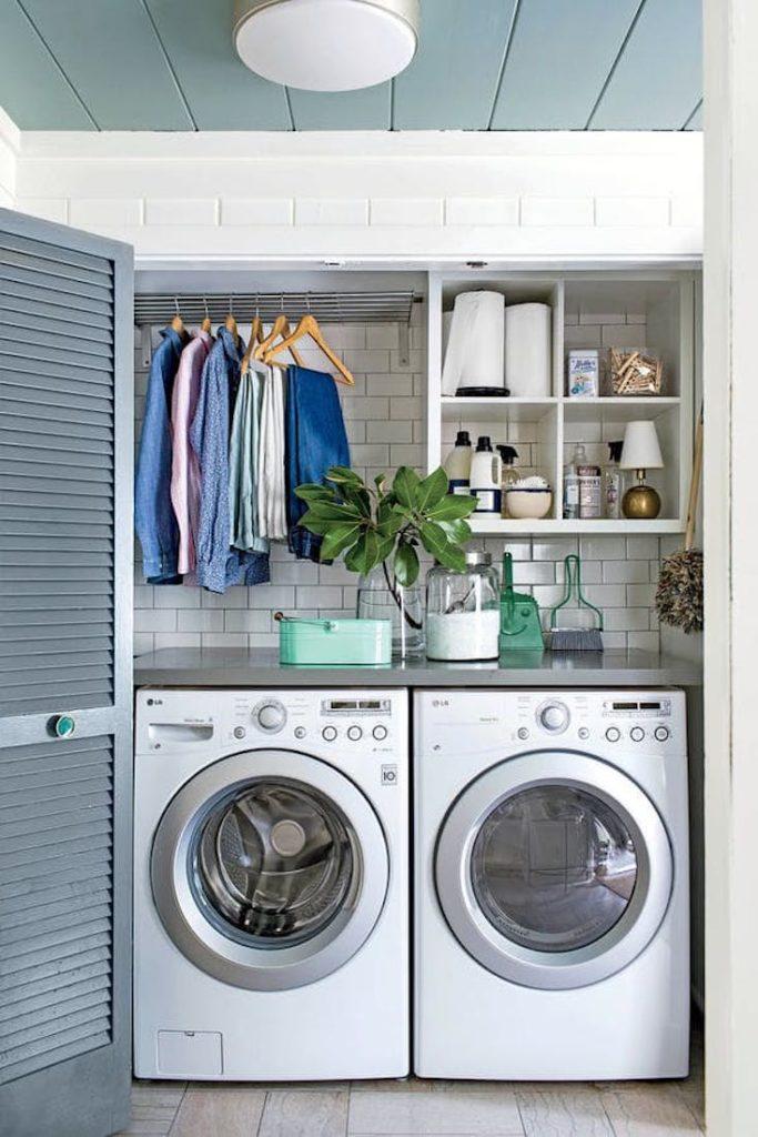 Área de serviço pequena com azulejo de tijolinho branco e porta retrátil.