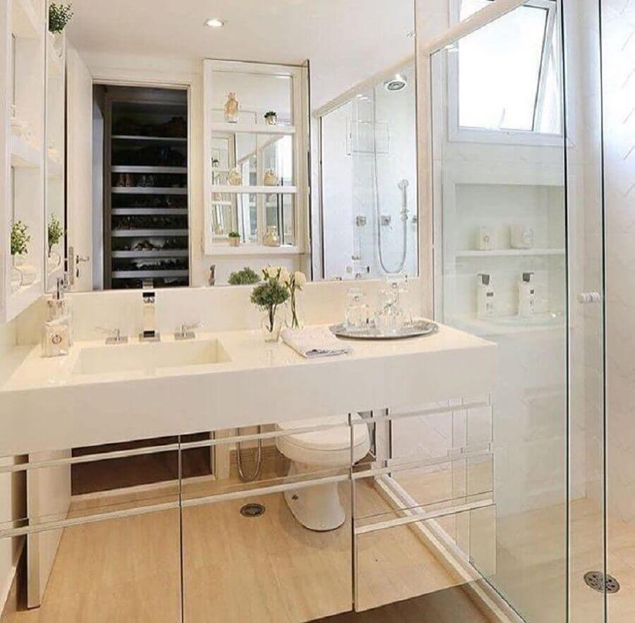 Decoração branca com armário espelhado.