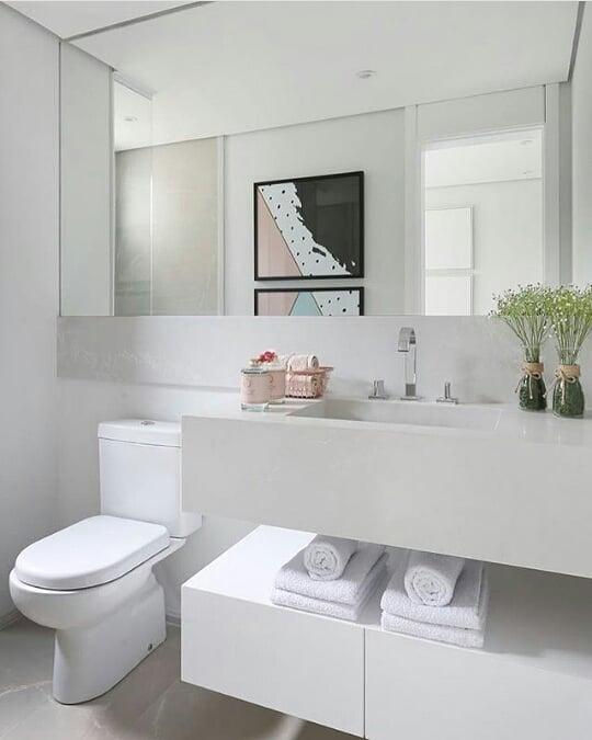 Decoração branca com armário moderno e pia esculpida.