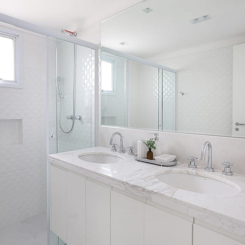 Decoração branca com bancada dupla e armário moderno.