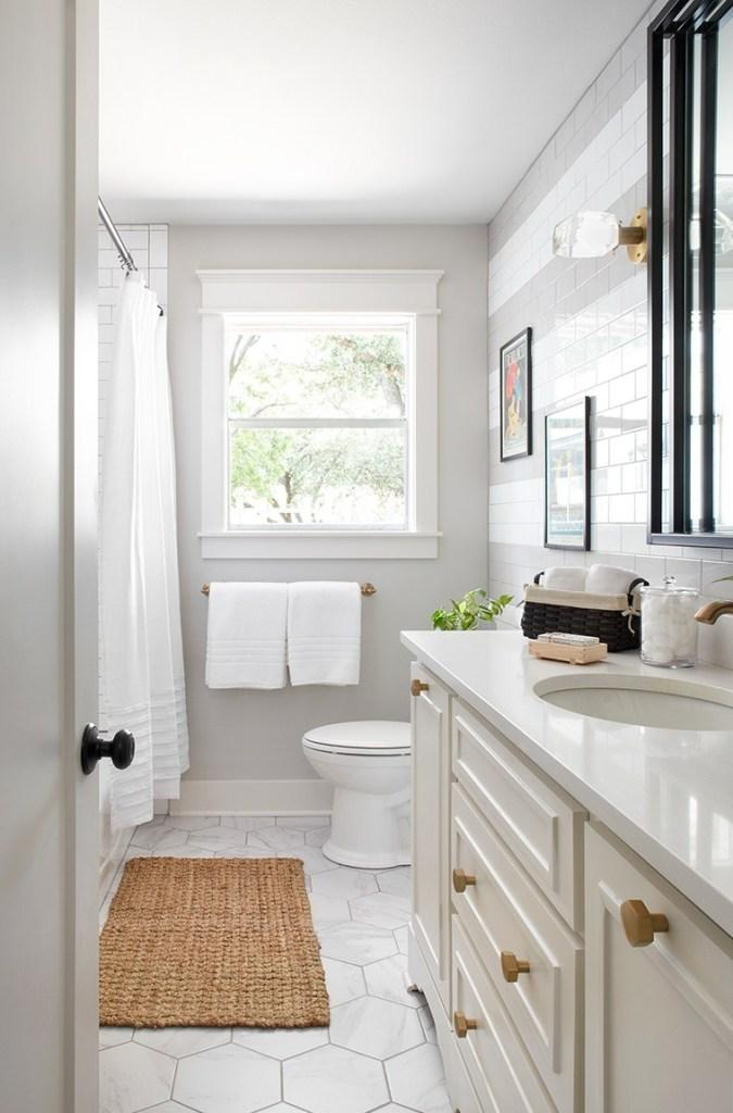 Decoração branca com armário clássico e revestimento hexagonal.