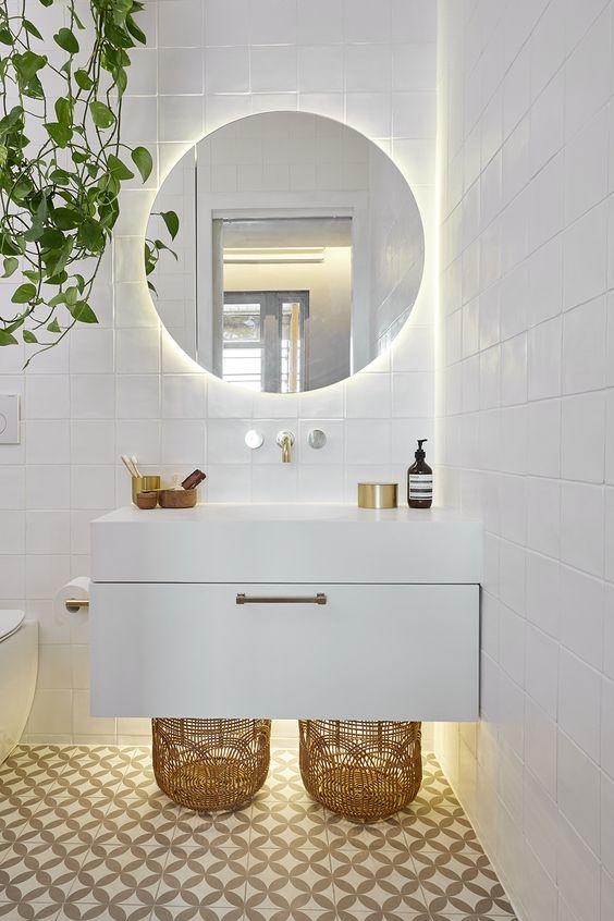 Decoração branca com armário moderno e espelho redondo.