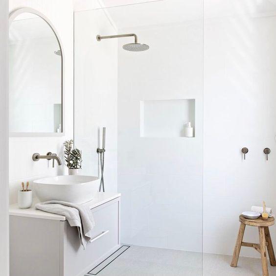Decoração branca e minimalista com armário moderno e cuba de apoio.