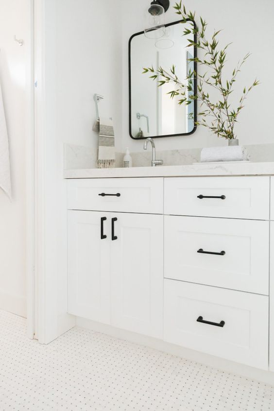 Decoração branca com armário moderno e puxador preto.