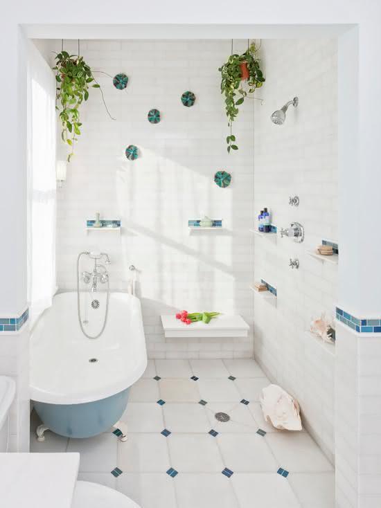 Decoração com banheira,pastilha azul e vasos de plantas suspensos.