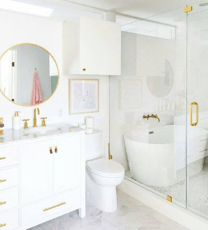 Banheiro branco com banheira e metais dourados.