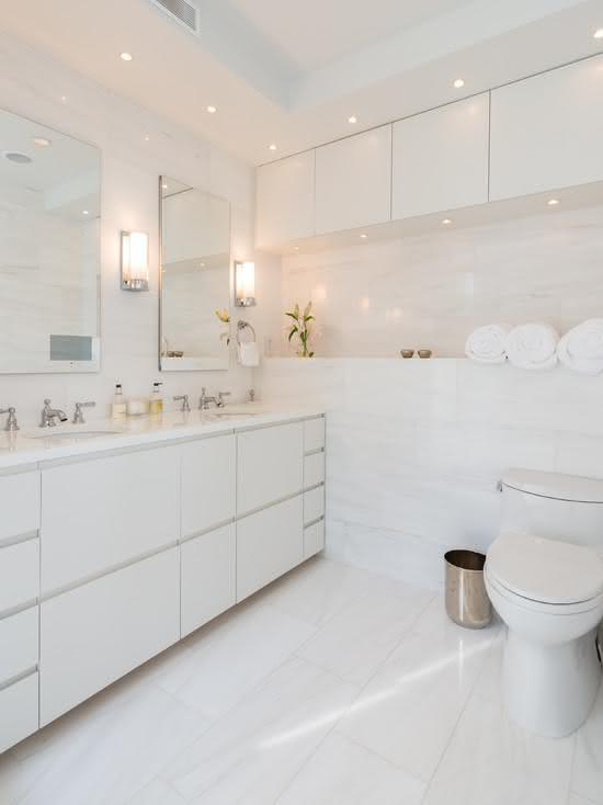 Banheiro branco com bancada dupla e spots de led.