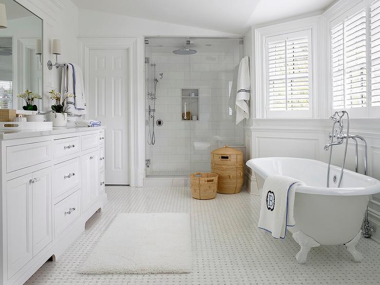 Banheiro branco com banheira e piso decorado.