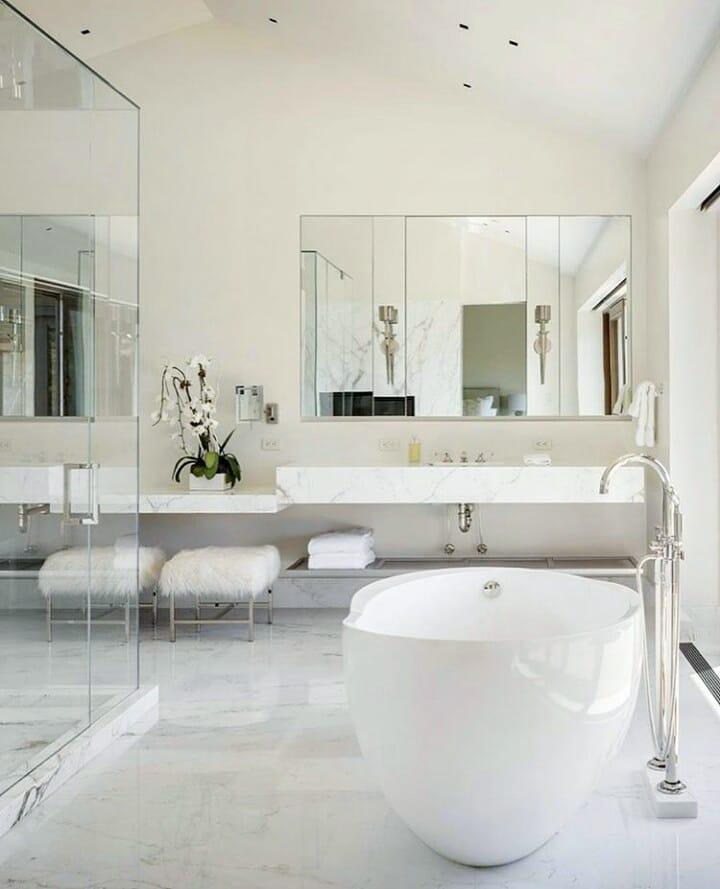Banheiro branco luxuoso com banheira e vaso de planta.
