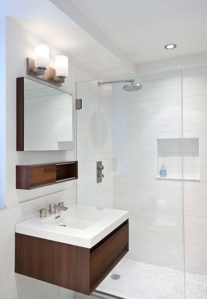 Banheiro branco com armário de madeira.