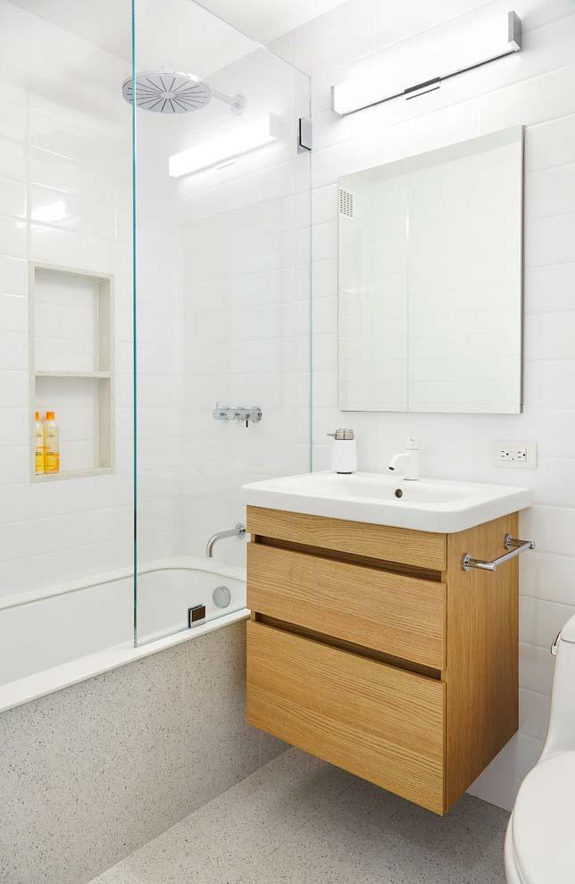 Banheiro branco com armário de madeira claro.