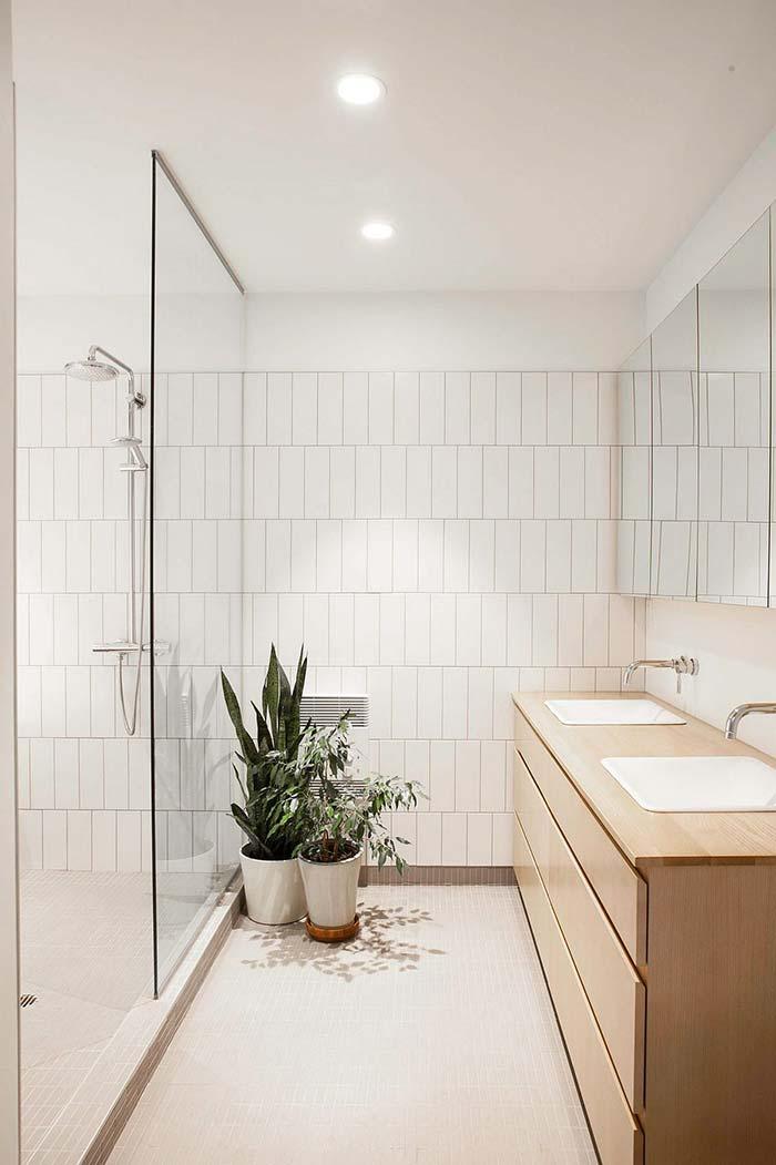 Banheiro branco com armário de madeira clara e bancada dupla.