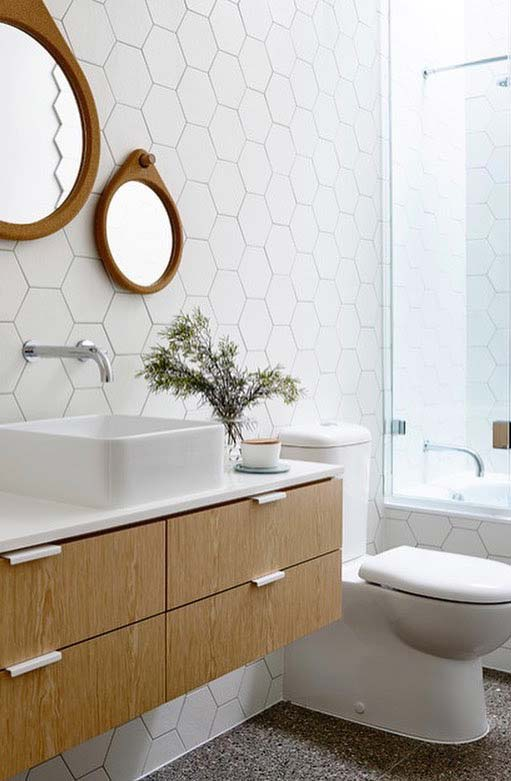 Banheiro branco com armário de madeira e azulejo hexogonal.