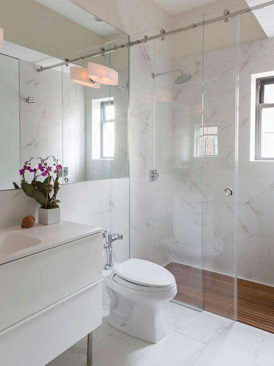 Banheiro branco pequeno com deck de madeira.