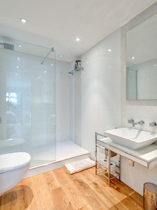 Banheiro branco com revestimento que imita madeira.