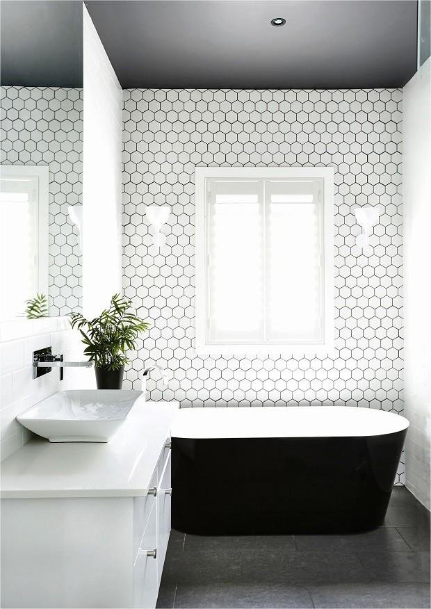 Banheiro branco e preto com banheiro e azulejo hexagonal.
