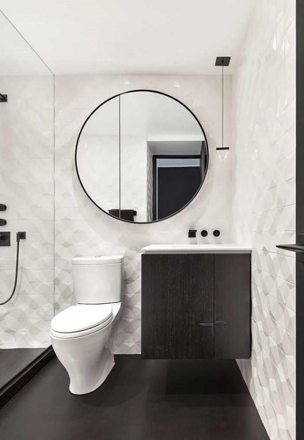 Banheiro branco e preto moderno com espelho redondo e azulejo tridimensional.