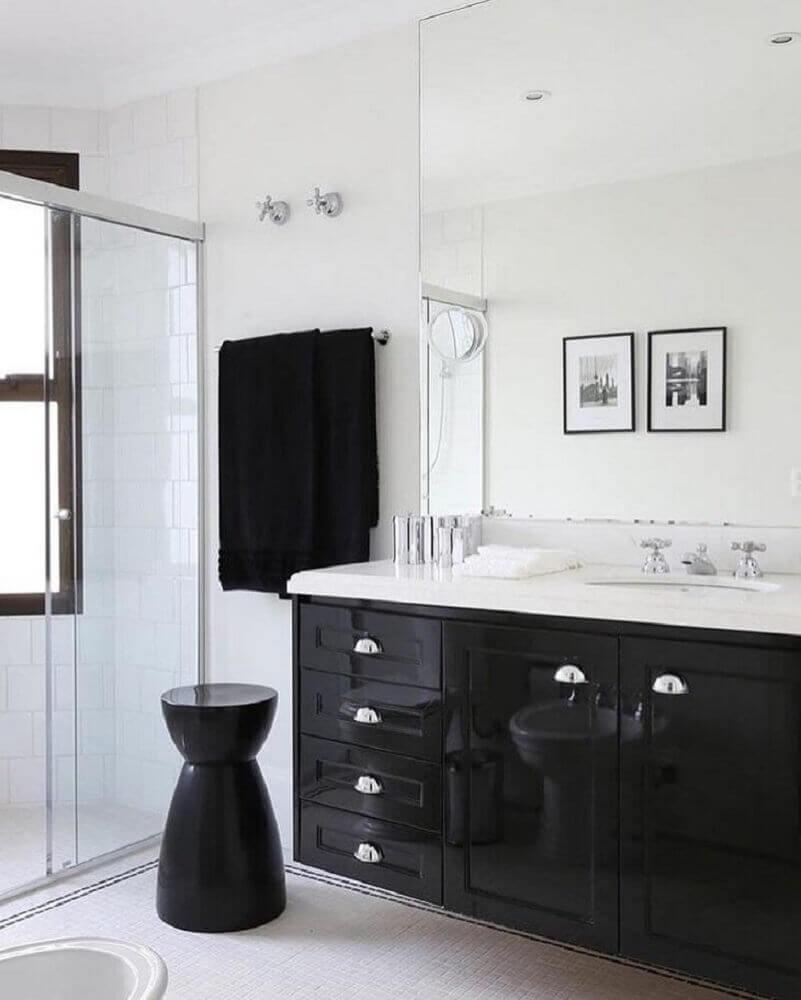 Banheiro branco e preto com armário preto.