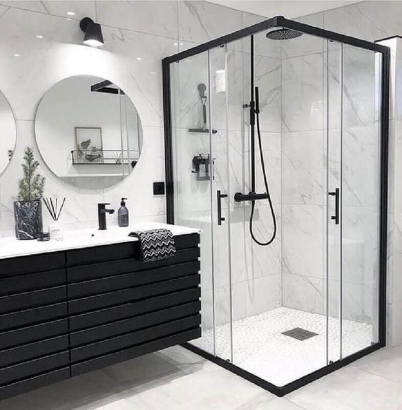 Banheiro branco e preto moderno com armário preto e espelho redondo.